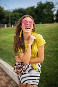 Portret van jonge stijlvolle vrouw met plezier in stadspark, lachende vrolijke stemming, positief, emotioneel, gele top, gestreepte minirok, handtas, roze zonnebril, zomer stijl modetrend dragen