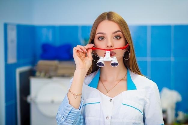 Portret van jonge stomatologist die grappig gezicht maakt terwijl het bekijken camera en het glimlachen.