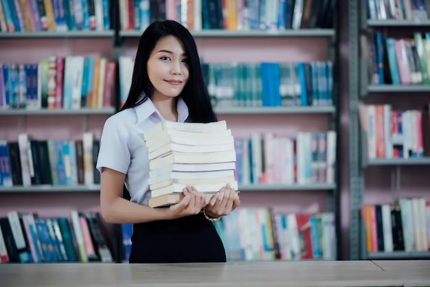 Portret van jonge student die een boek in een bibliotheek leest