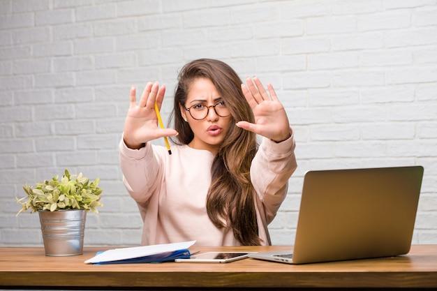 Portret van jonge student latijnse vrouw zittend op haar bureau serieus en vastberaden, hand in de voorkant, stop gebaar, ontkennen concept