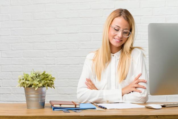 Portret van jonge studentenzitting op haar bureau die taken doen die omhoog eruit zien