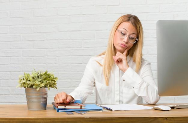 Portret van jonge studentenzitting op haar bureau die taken doen die twijfelen en verward, aan een idee denken of zich over iets ongerust maken