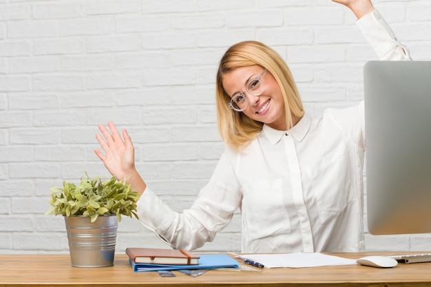 Portret van jonge studentenzitting op haar bureau die taken doen zeer gelukkig en opgewekt