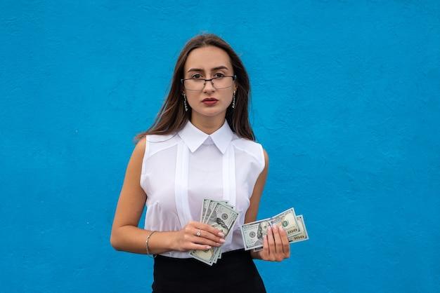 Portret van jonge succes zakenvrouw houdt veel geld dollarbiljetten geïsoleerd op blue