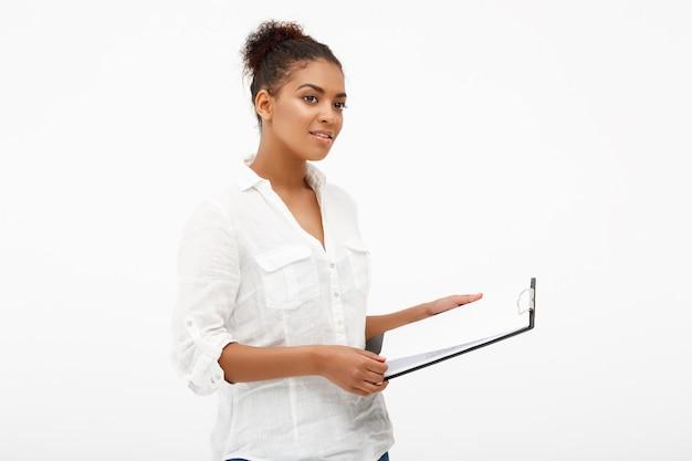 Portret van jonge succesvolle afrikaanse zakelijke dame over witte muur