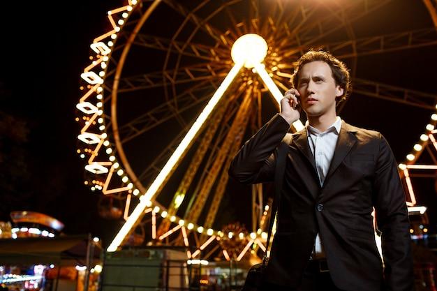 Portret van jonge succesvolle zakenman over nachtpretpark. ondiepe dof