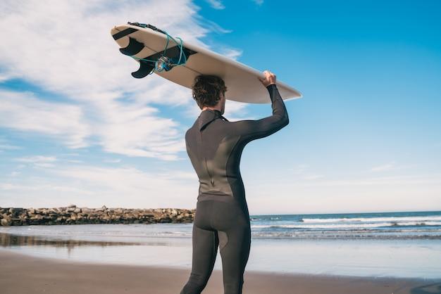 Portret van jonge surfer bij het strand dat zijn surfplank steunt en een zwart surfend kostuum draagt. sport en watersport concept.