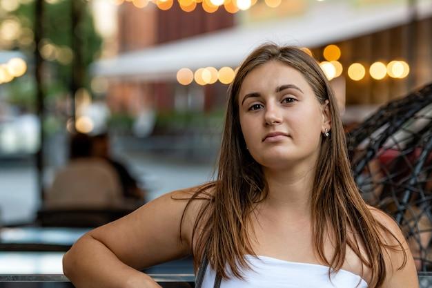 Portret van jonge swoman over wazig slingers van lichten op straat