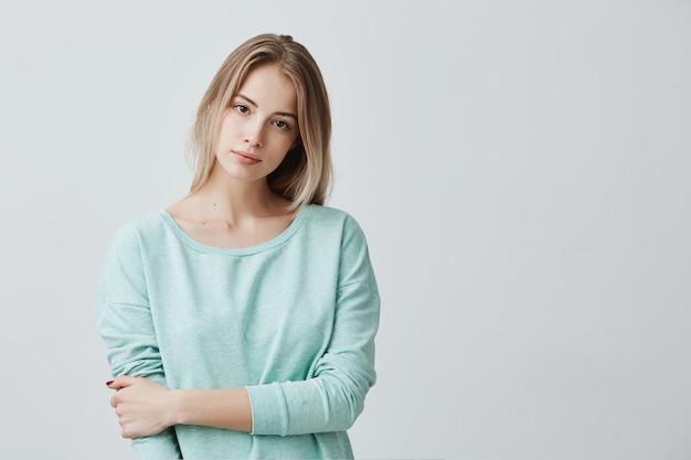 Portret van jonge tedere blonde europese vrouw die het lichtblauwe ernstig kijken dragen met lange mouwen