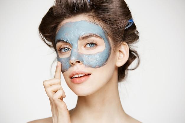 Portret van jonge tedere vrouw in haarkrulspelden en gezichtsmasker glimlachen. schoonheid en huidverzorging concept.