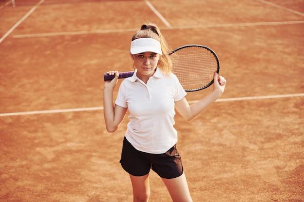 Portret van jonge tennisspeelster in sportieve kleding is buiten op het veld.