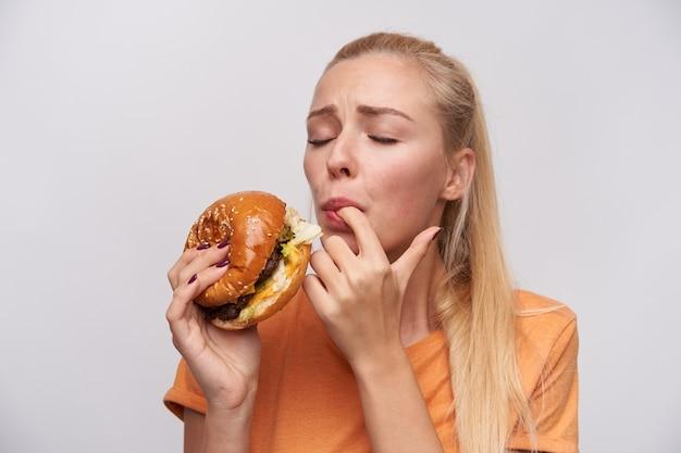 Portret van jonge tevreden blonde vrouw met casual kapsel, proeft haar verse hamburger met veel plezier en houdt de ogen gesloten, staande tegen een witte achtergrond