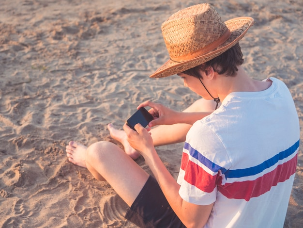 Portret van jonge tiener playin met zijn telefoon op het zandige strand in de zomerhoed