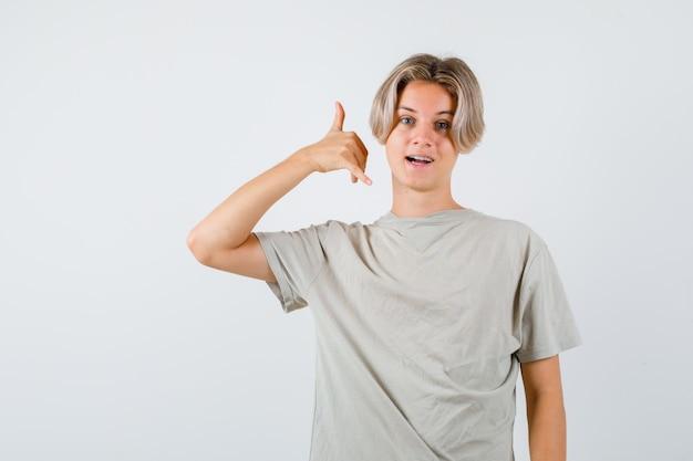 Portret van jonge tienerjongen die telefoongebaar in t-shirt toont en vrolijk vooraanzicht kijkt