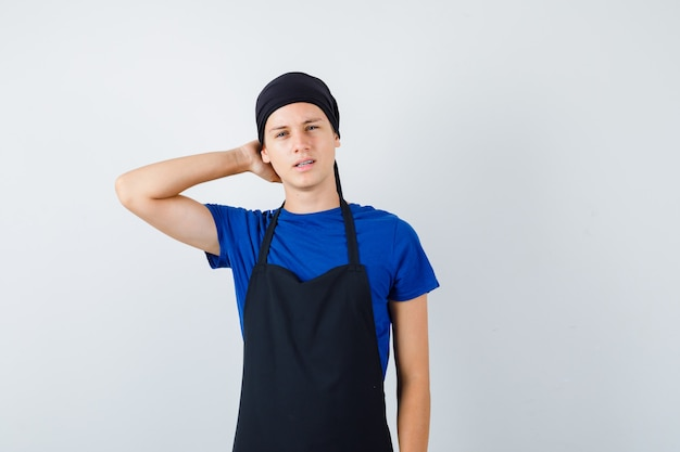 Portret van jonge tienerkok met hand achter hoofd in t-shirt, schort en peinzend vooraanzicht