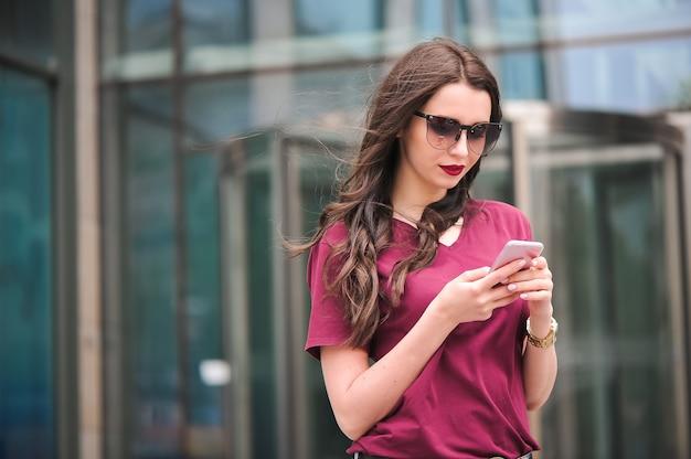 Portret van jonge toerist in de stad met behulp van mobiele telefoon