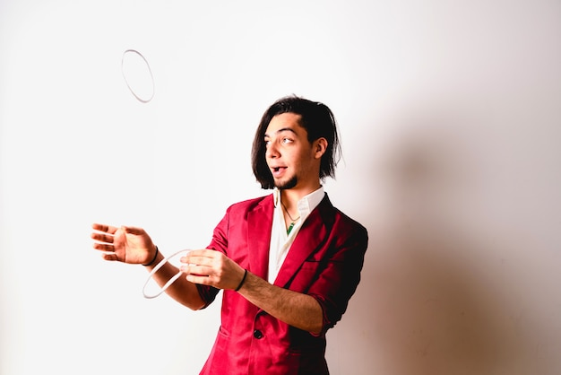 Portret van jonge tovenaar die kabels en bandanas behandelen om magische trucs te doen, dat op wit wordt geïsoleerd.