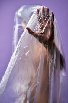 Portret van jonge transgender met doorzichtige plastic zak op lichaam close-up stop handsymbool