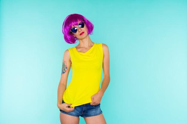 Portret van jonge transgendervrouw met een probleemhuid in roze pruik en zonnebrilhartvorm op blauwe achtergrond