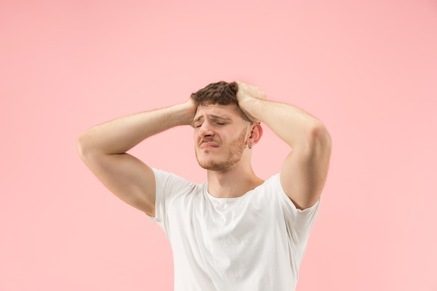 Portret van jonge trendy man op roze achtergrond. emotionele uitdrukking.