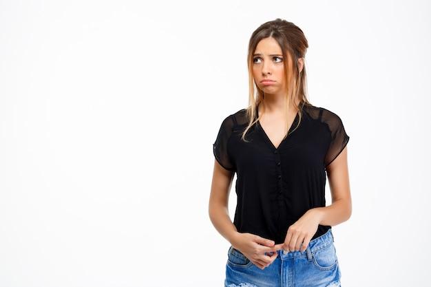 Portret van jonge triest mooi meisje op witte achtergrond. kopieer ruimte.
