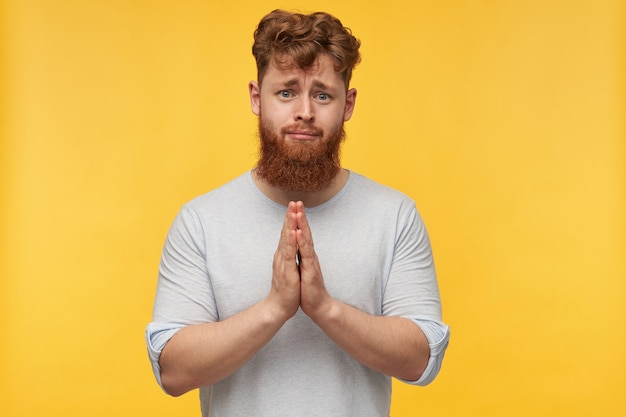 Portret van jonge trieste man, met rood haar en grote baard, houdt zijn handpalm bij elkaar in biddend gebaar, voelt zich omhelsd, alsjeblieft iemand op geel.