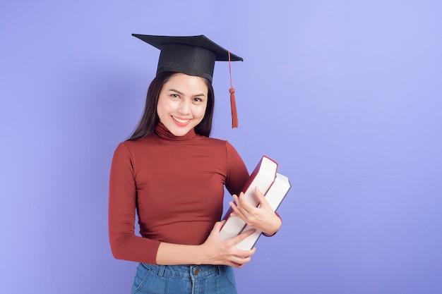 Portret van jonge universiteitsstudent vrouw met afstuderen cap
