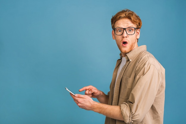 Portret van jonge verbaasd geschokt man in casual sms te typen. telefoon gebruiken.