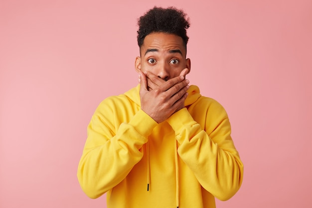 Portret van jonge verbaasde afro-amerikaanse man in gele hoodie, bedekte zijn mond met hand in shock