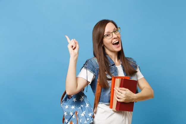 Portret van jonge verbaasde geamuseerde studente in glazen met rugzak met boeken, wijsvinger omhoog wijzend op kopieerruimte geïsoleerd op blauwe achtergrond. onderwijs in middelbare school hogeschool.