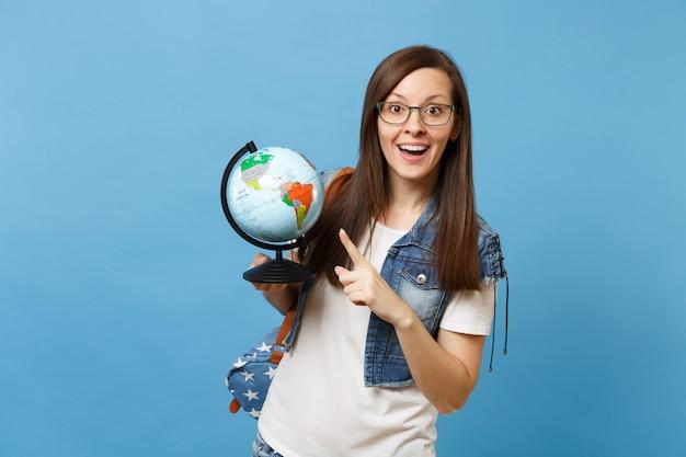 Portret van jonge verbaasde gelukkige vrouw student in glazen met rugzak wijzende wijsvinger op wereldbol leren aardrijkskunde geïsoleerd op blauwe achtergrond. onderwijs in middelbare school hogeschool.