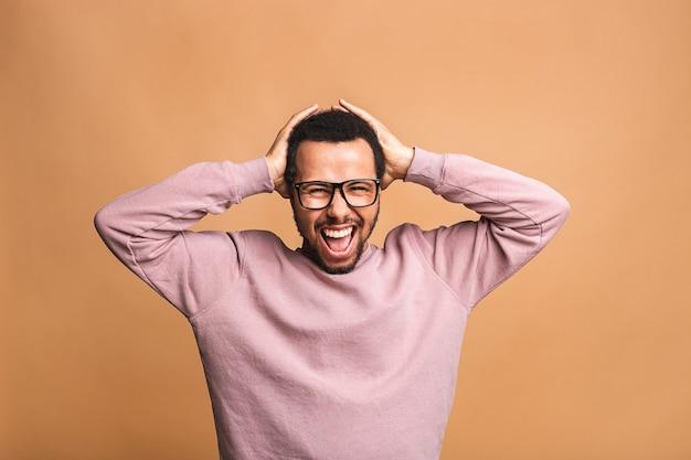 Portret van jonge verbaasde man met afro kapsel in casual, in de camera kijken met geopende mond en geschokte uitdrukking