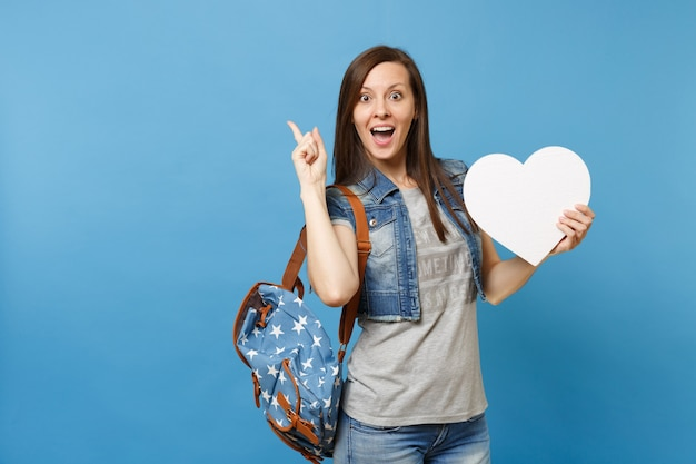 Portret van jonge verbaasde vrouw student met rugzak met wit hart met kopie ruimte wijzende wijsvinger opzij geïsoleerd op blauwe achtergrond. onderwijs aan de universiteit. kopieer ruimte voor advertentie.