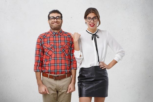 Portret van jonge verlegen nerd man met bril ziet er onhandig uit, heeft een idiote uitdrukking