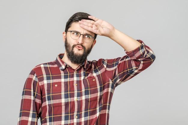 Portret van jonge vermoeide kaukasische kerel die zijn voorhoofd met hand afveegt
