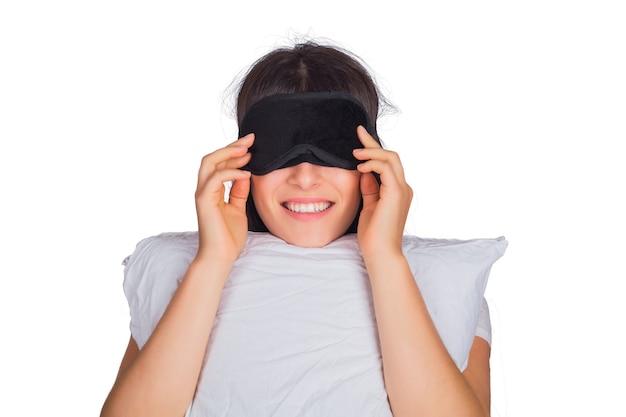 Portret van jonge vermoeide vrouw die slaapmasker draagt en een hoofdkussen op studio houdt.