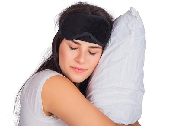 Portret van jonge vermoeide vrouw die slaapmasker draagt, rust en een hoofdkussen op studio houdt.
