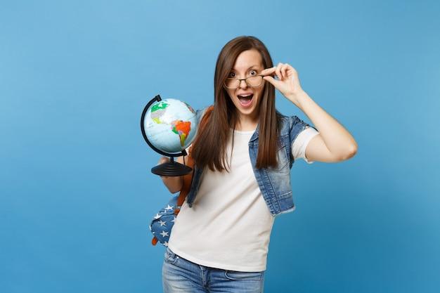 Portret van jonge verraste verbaasde studente met geopende mond met rugzak die een bril verwijdert met wereldbol geïsoleerd op blauwe achtergrond. onderwijs in het concept van de middelbare schooluniversiteit.