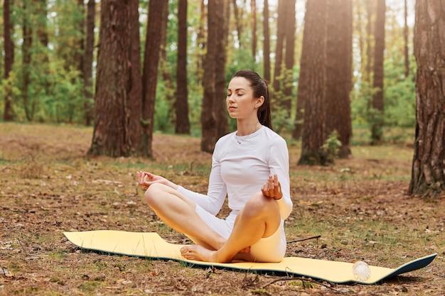 Portret van jonge volwassen vrouw in witte top en leggins zittend op mat met gekruiste benen in lotushouding en mediteren, ogen gesloten houden