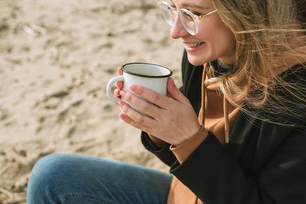 Portret van jonge volwassen vrouw met emaille mok met warme drank zittend op een strand