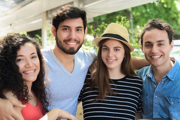 Portret van jonge vrienden die bij camera glimlachen