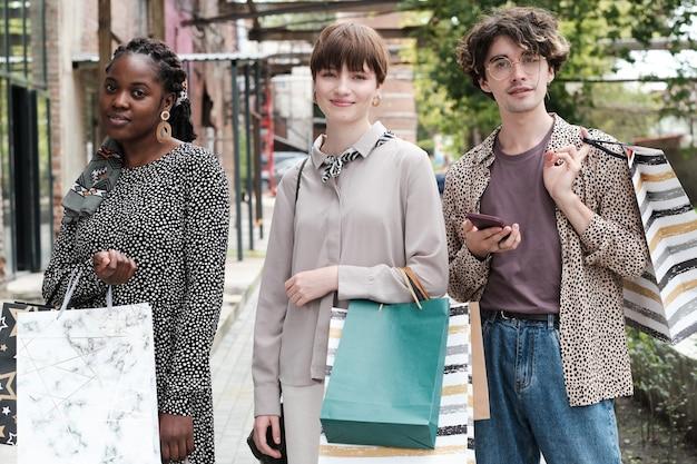 Portret van jonge vrienden met boodschappentassen die naar de camera kijken terwijl ze samen winkelen in de stad