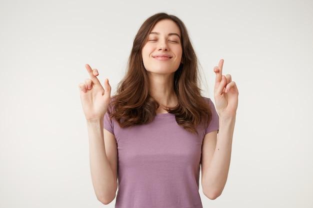 Portret van jonge vrij geïnspireerde vrouw die een wens doet met gekruiste vingers, gesloten ogen, hoopvol gebaar