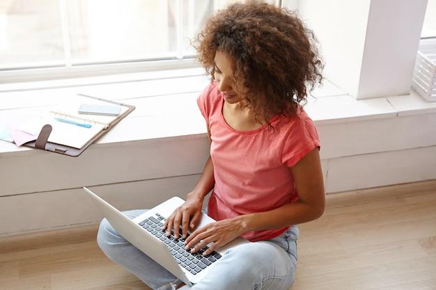 Portret van jonge vrij gekrulde vrouw met donkere huid zittend op de vloer met laptop, handen houden op toetsenbord, poseren voor breed raam, spijkerbroek en roze t-shirt dragen