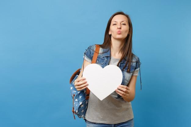 Portret van jonge vrij grappige vrouw student met rugzak met wit hart met kopie ruimte waait lippen zoenen geïsoleerd op blauwe achtergrond. onderwijs op de middelbare school. kopieer ruimte voor advertentie.