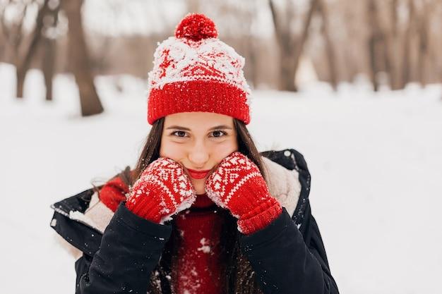 Portret van jonge vrij lachende gelukkige vrouw in rode wanten en gebreide muts dragen winterjas, wandelen in het park in de sneeuw, warme kleren, grappig gezicht expressie, moe