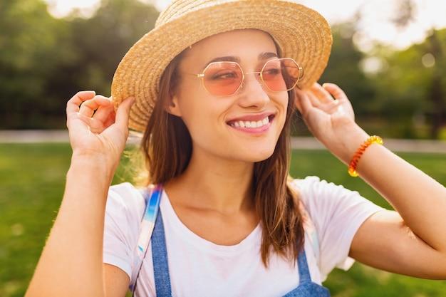 Portret van jonge vrij lachende vrouw in strohoed en roze zonnebril wandelen in het park, zomer mode-stijl, kleurrijke hipster outfit