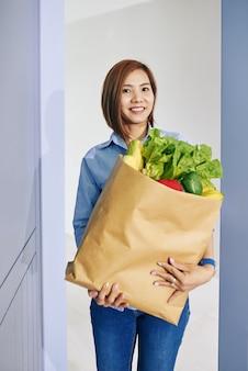 Portret van jonge vrij vietnamese vrouw die groot pakket verse boodschappen houdt en bij camera glimlacht