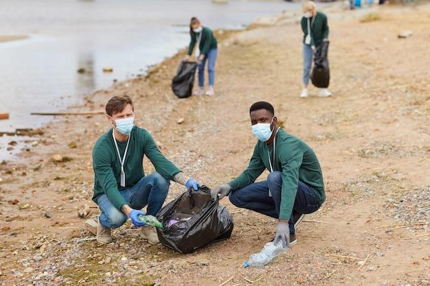 Portret van jonge vrijwilligers die het vuilnis oppakken in zakken die ze de zee buitenshuis schoonmaken