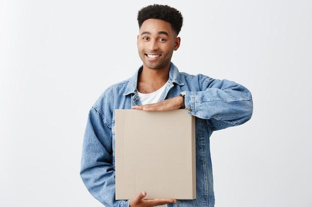 Portret van jonge vrolijke aantrekkelijke donkere man met afro kapsel in wit overhemd en blauwe jas houden papier doos in handen met heldere glimlach en gelukkige uitdrukking